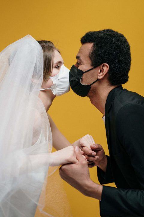 man-in-black-suit-jacket-holding-woman-in-white-wedding-3951880